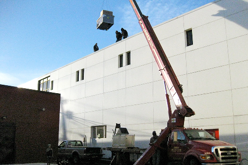 HVAC roof-top unit gets hoisted up early in the morning.